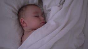 Un enfant en bas âge de sommeil mignon se trouvant sous une couverture blanche dans le mouvement lent banque de vidéos