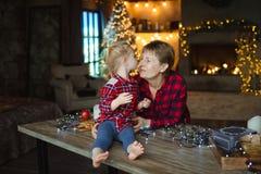 Un enfant en bas âge doux embrasse sa grand-mère dans le nez, se reposant sur une table en bois dans une maison de chasse décorée image libre de droits