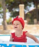 Un enfant en bas âge heureux joue dehors dans une piscine de bébé Photos libres de droits