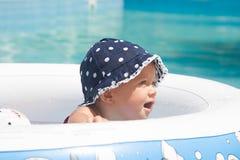 Un enfant en bas âge heureux joue dehors dans une piscine de bébé Image stock