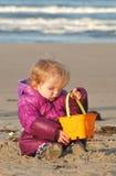 Un enfant en bas âge joue avec un seau de sable à la plage Photographie stock libre de droits