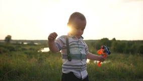 Un enfant en bas âge mignon joue avec un tracteur sur la nature au coucher du soleil dans le mouvement lent banque de vidéos