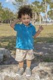 Un enfant en bas âge se tient sur une grande roche au parc regardant la caméra images libres de droits