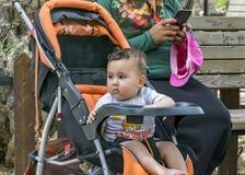 Un enfant a ennuyé la séance dans une poussette de bébé Une mère féminine habillée dans l'habillement musulman traditionnel utili photos stock