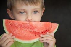 Un enfant et un morceau de pastèque photos stock