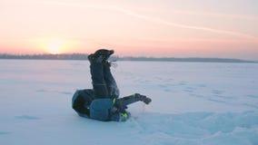 Un enfant fait des sauts périlleux dans la neige au coucher du soleil Amusement et jeux à l'air frais banque de vidéos