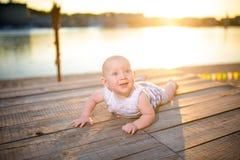 Un enfant un garçon, un an, homme blond se trouve sur son estomac sur le dock en bois, le pilier dans des vêtements rayés, compos Photo libre de droits