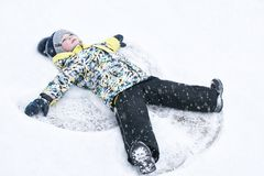 Un enfant, un garçon, mensonges sur la neige, fait un ange de neige avec ses bras et jambes, émotions, rires Photographie stock libre de droits