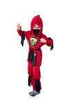 Un enfant habillé dans le costume rouge de ninja Photographie stock libre de droits