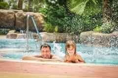 Un enfant heureux avec un parent dans une piscine par la mer images stock
