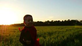 Un enfant heureux dans un costume de super héros dans un manteau rouge court à travers une pelouse verte pendant le coucher du so banque de vidéos