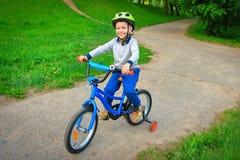 Un enfant heureux monte la bicyclette en parc vert de ville dehors sur un sentier piéton Photo libre de droits