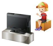 Un enfant heureux regardant la TV Image libre de droits