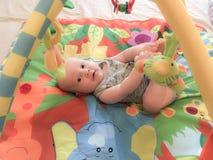 Un enfant heureux se trouvant et jouant image libre de droits
