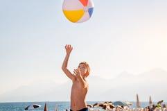 Un enfant jouant avec du ballon de plage Image stock