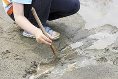 Un enfant jouant avec un bâton dans la boue photos stock