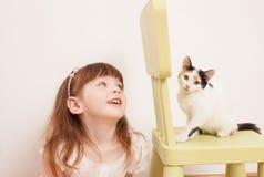 Un enfant jouant avec un chaton blanc Image stock