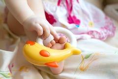 Un enfant jouant avec un jouet, le met sur la jambe Image stock