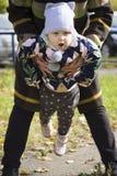 Un enfant jouant en parc avec la famille Image stock
