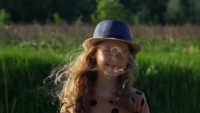 Un enfant joyeux dans un chapeau d'été regarde dans l'appareil-photo par temps venteux banque de vidéos