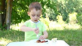 Un enfant mange de la viande de rôti avec plaisir, chiche-kebab, se repose à une table de touristes en nature clips vidéos