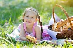 Un enfant mange du pain se reposant sur l'herbe Image stock