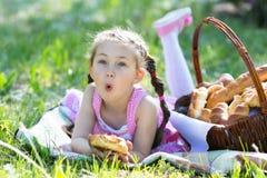 Un enfant mange du pain se reposant sur l'herbe Photos libres de droits