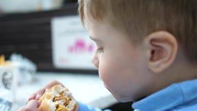 Un enfant mange un petit pain avec une c?telette et un fromage dans un restaurant d'aliments de pr?paration rapide banque de vidéos