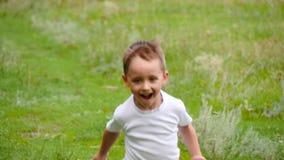 Un enfant mignon court par l'herbe verte à proximité de la forêt banque de vidéos