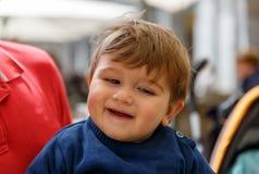 Un enfant mignon sourit tandis que dans les bras d'un adulte Image stock