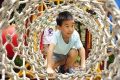 Un enfant montant une gymnastique de jungle. Photographie stock libre de droits