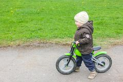 Un enfant montant un vélo sans pédale Un petit garçon apprend à photographie stock