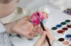 Un enfant peint des oeufs avec une brosse Peignez les oeufs pour Pâques images libres de droits