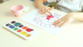 Un enfant peint des tableaux d'un doigt avec des aquarelles banque de vidéos