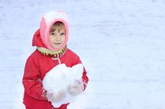 Un enfant regarde dans l'appareil-photo, neige, dans des ses mains une boule de neige, sur un fond de la neige blanche Photo stock
