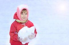 Un enfant regarde dans l'appareil-photo, neige, dans des ses mains une boule de neige, sur un fond de la neige blanche Photo libre de droits