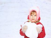 Un enfant regarde dans l'appareil-photo, neige, dans des ses mains une boule de neige, sur un fond de la neige blanche Photos libres de droits