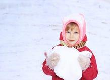 Un enfant regarde dans l'appareil-photo, neige, dans des ses mains une boule de neige, sur un fond de la neige blanche Photographie stock libre de droits