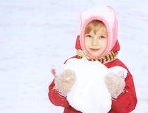 Un enfant regarde dans l'appareil-photo, neige, dans des ses mains une boule de neige, sur un fond de la neige blanche Image libre de droits