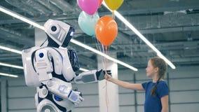 Un enfant renonce à des ballons à un robot blanc, fin clips vidéos