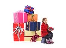 Un enfant retenant un cadeau à côté d'une pile des cadeaux Photo stock
