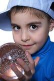 Un enfant retient une bille en verre. photo stock