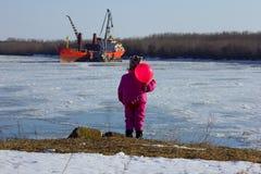 Un enfant se tient avec une boule rouge et regarde le bateau Photo stock
