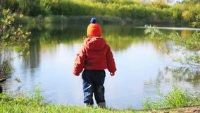 Un enfant se tient sur la banque de l'étang et des pierres de lancement Promenades à l'air frais banque de vidéos