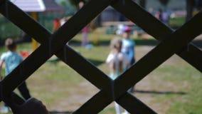 Un enfant seul tient une barrière et des regards au jeu d'enfants Macro mains banque de vidéos