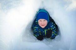 Un enfant sort de la caverne de neige image stock