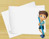 Un enfant tenant un crayon près des papiers vides Photo libre de droits