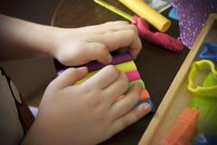 Un enfant travaillant avec de la p?te ? modeler photographie stock