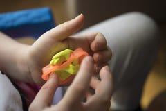 Un enfant travaillant avec de la p?te ? modeler image stock