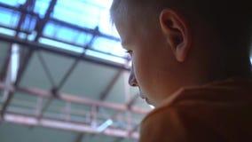 Un enfant triste voit outre de quelqu'un à l'aéroport, un profil du ` s de garçon, espoirs cassés par s de ` d'enfants banque de vidéos